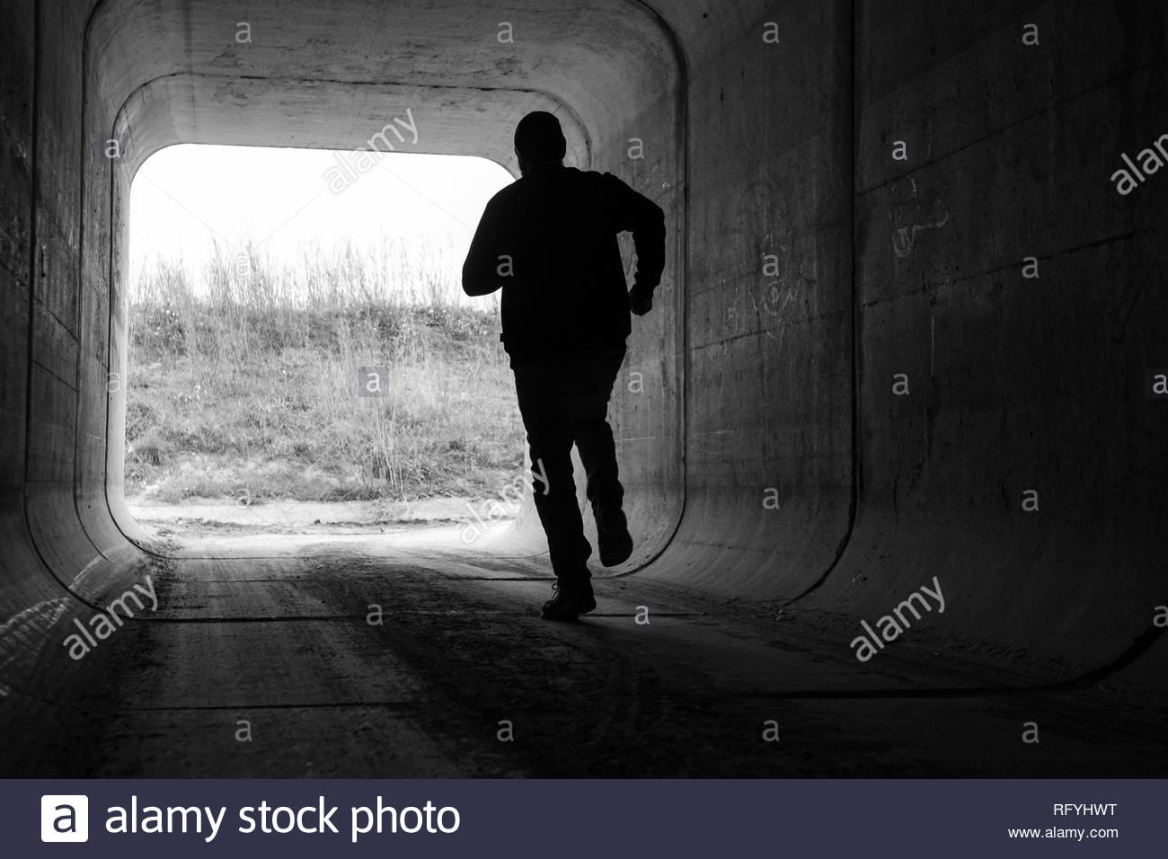 man running through dark tunnel escaping Stock Photo