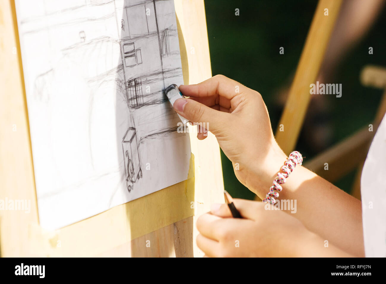 artist drawing a pencil on the street on sunny summer day. hand closeup Stock Photo