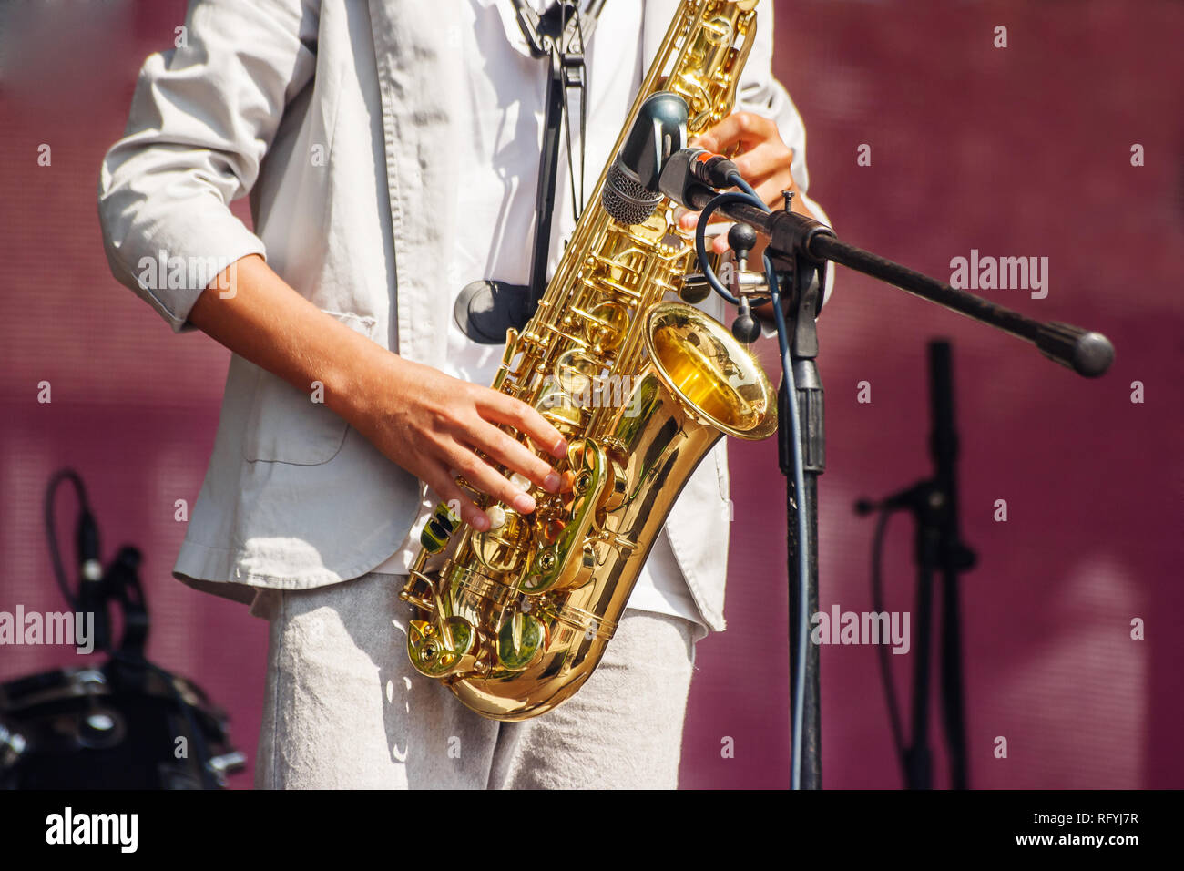 saxophonist playing at a jazz festival in a city park on sunny summer day - Stock Image