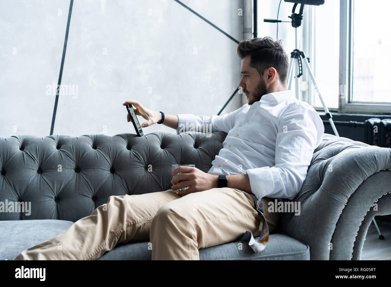 focused handsome man in formal wear sitting on gray sofa and using smartphone. - Stock Image