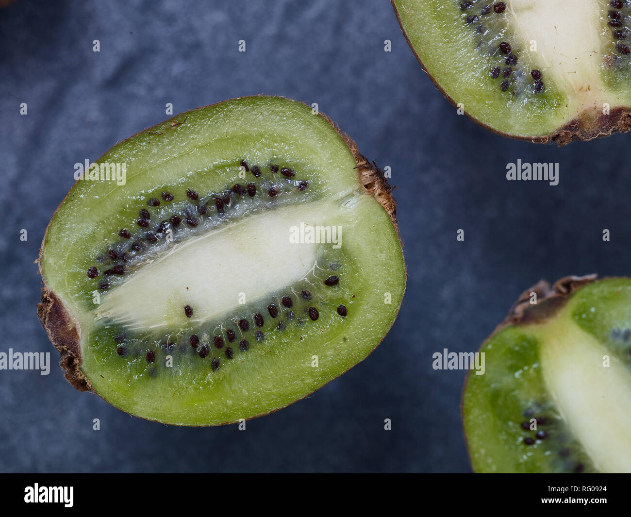 Cut Kiwi-fruit against black background still-life food photograph - Stock Image