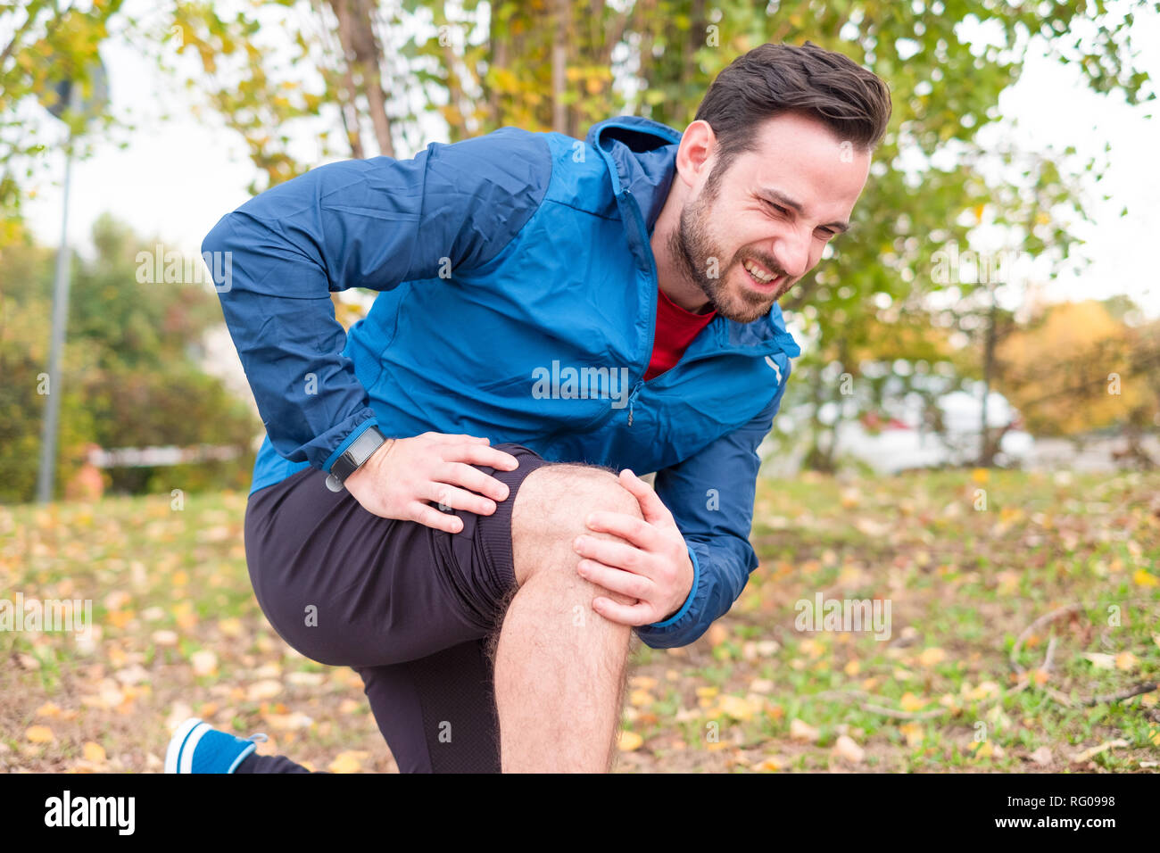 Athlete running outdoor and suffering for leg pain - Stock Image
