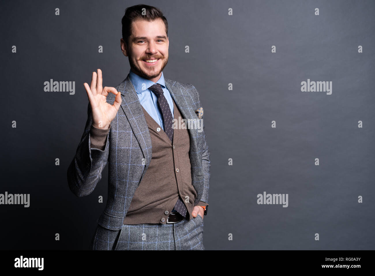 Portrait of excited satisfied cheerful confident positive handsome demonstrating thumbs-up pointing up isolated on gray background. - Stock Image