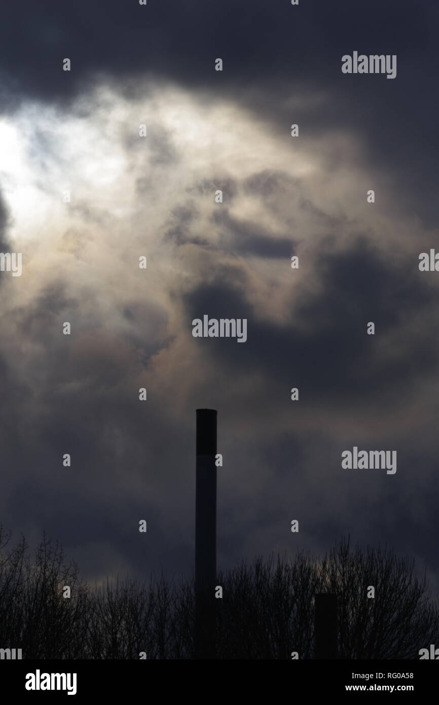 Silhouetted Factory Chimney at Secanim Ltd, Marsh Barton, Exeter Devon, UK. On a Gloomy Winters Day. - Stock Image