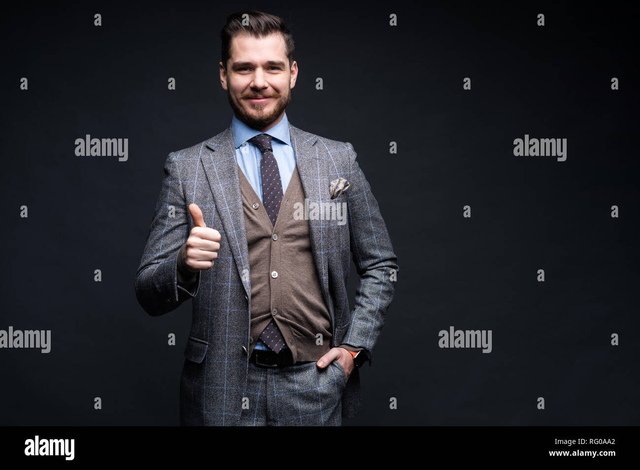 Portrait of excited satisfied cheerful confident positive handsome demonstrating thumbs-up pointing up isolated on black background. - Stock Image