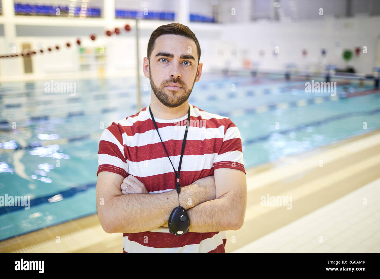 Young trainer standing in the pool - Stock Image