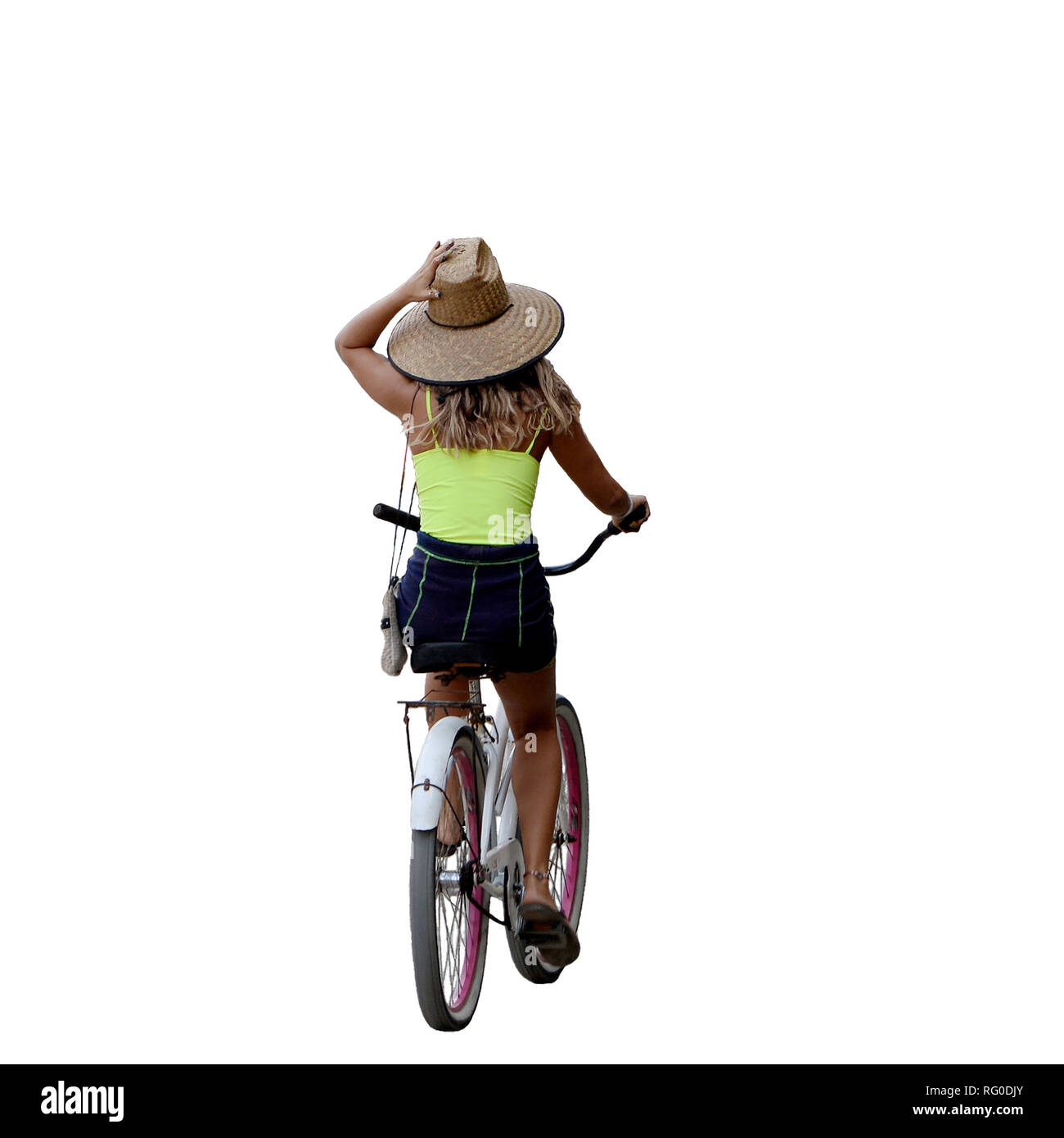 Hold onto your hat Pura Vida style .Girl in summer clothing, cycles away with one hand holding hat and steering with the other in Costa Rica. - Stock Image
