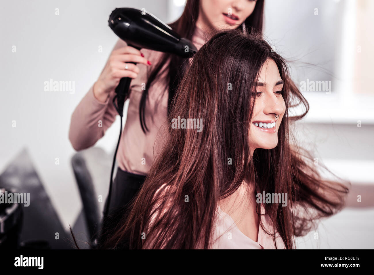 Delighted cheerful woman being in the hairdresser salon - Stock Image