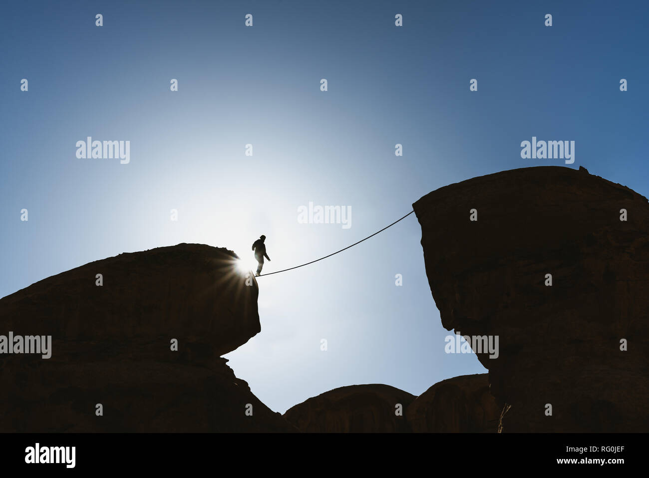 a man balancing walking on rope over precipice. Business, risk taking, challenge,bravery, and concentration - Stock Image