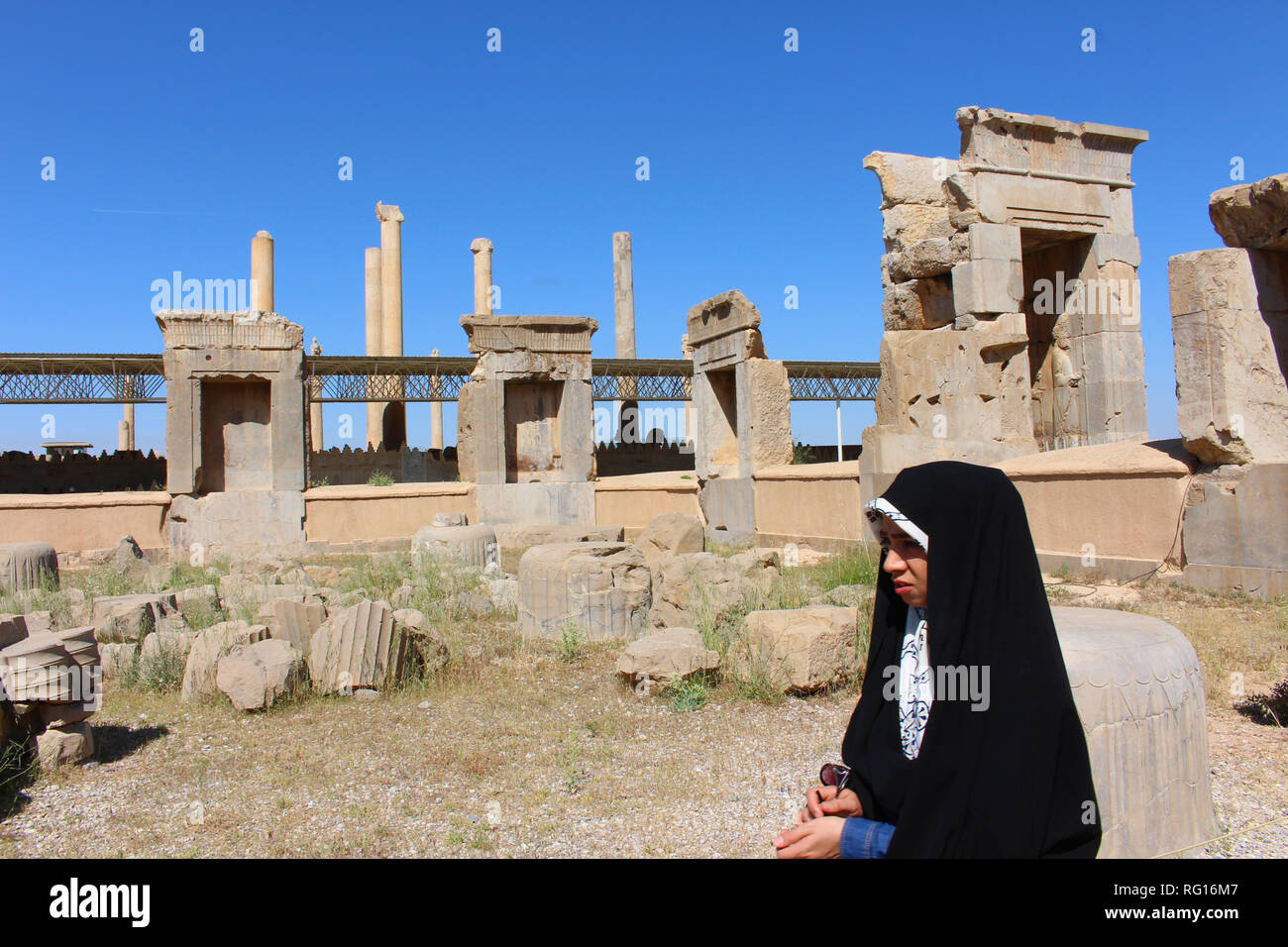 An Iranian girl in front of the ruins of the ceremonial capital of the Achaemenid Empire, Iran - Stock Image