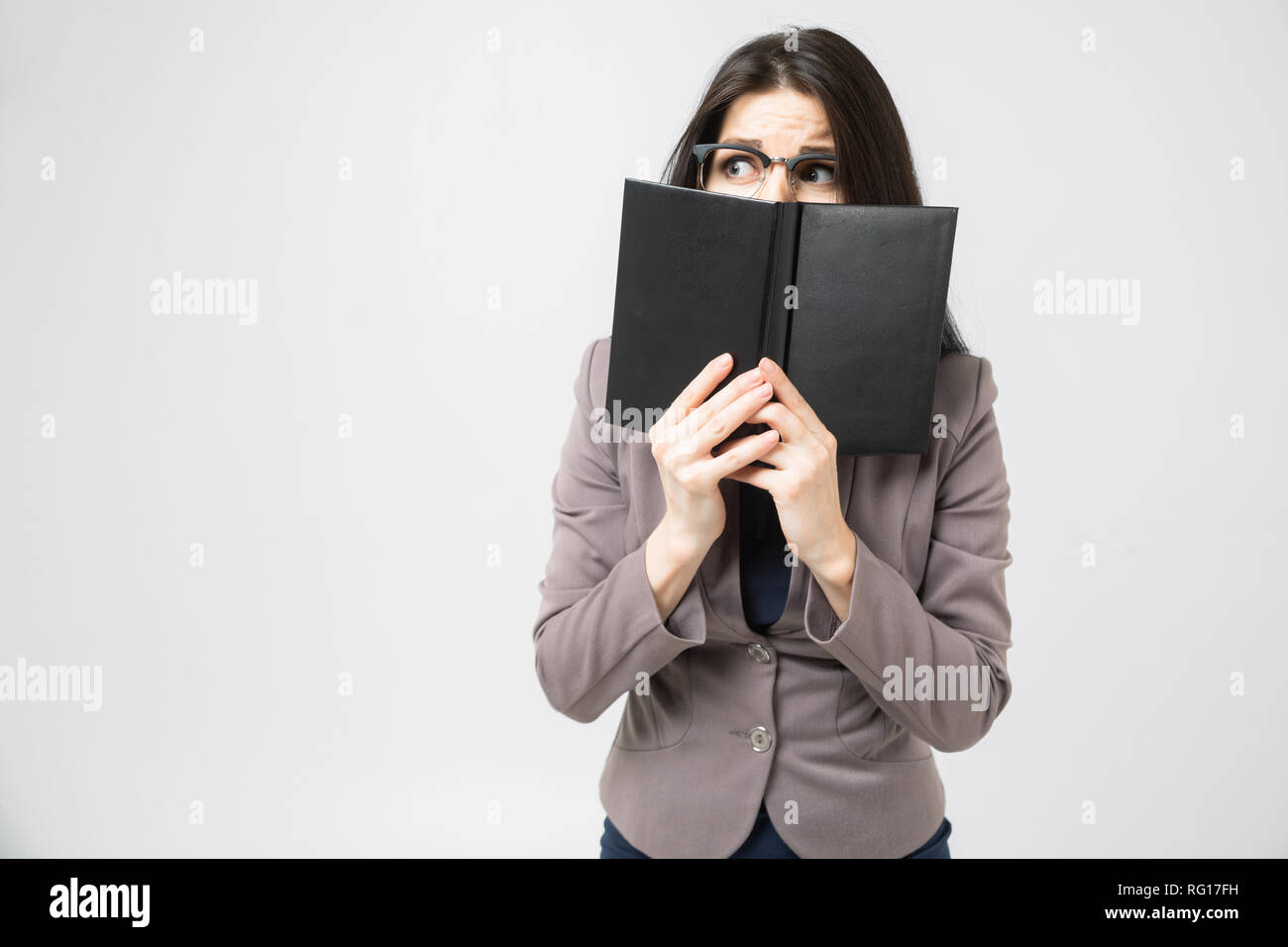 Young brunette covered the floor of her face with a diary isolated on a white background - Stock Image