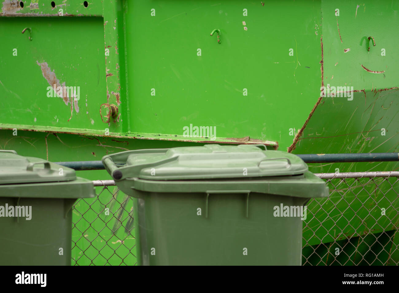 green trash can in front of a green trash container - Stock Image