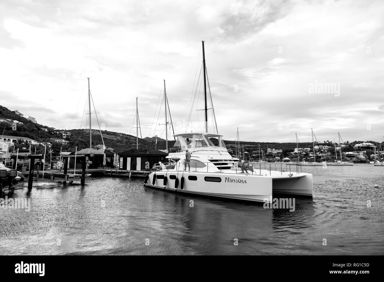 Philipsburg, Sint Maarten - January 24, 2016: yacht anchored at sea pier. People sit on modern ship deck. Luxury travel on yacht, wanderlust. Summer vacation at Caribbean. Water transport and vessel. - Stock Image