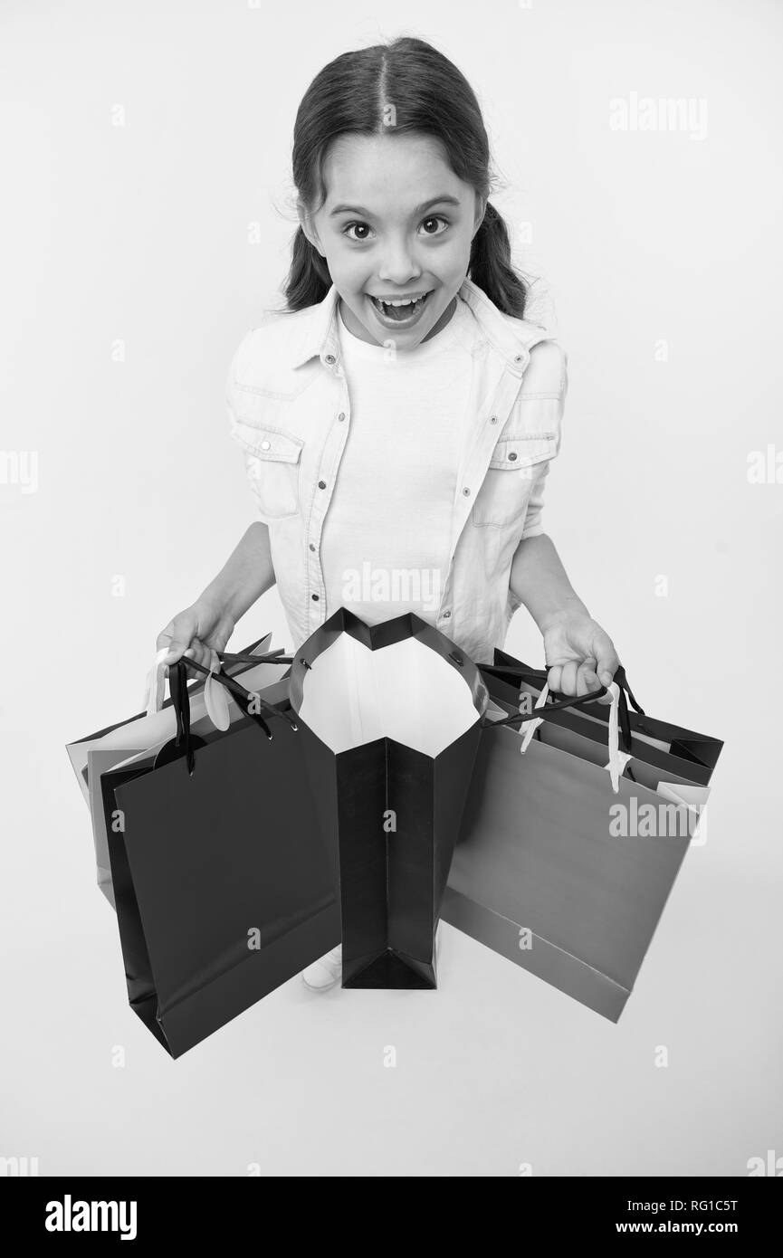 Check out her profitable purchases. Girl carries shopping bags yellow background. Girl fond of shopping. Child cute shopaholic with bunch shopping bags black friday total sale. Exciting shopping. - Stock Image