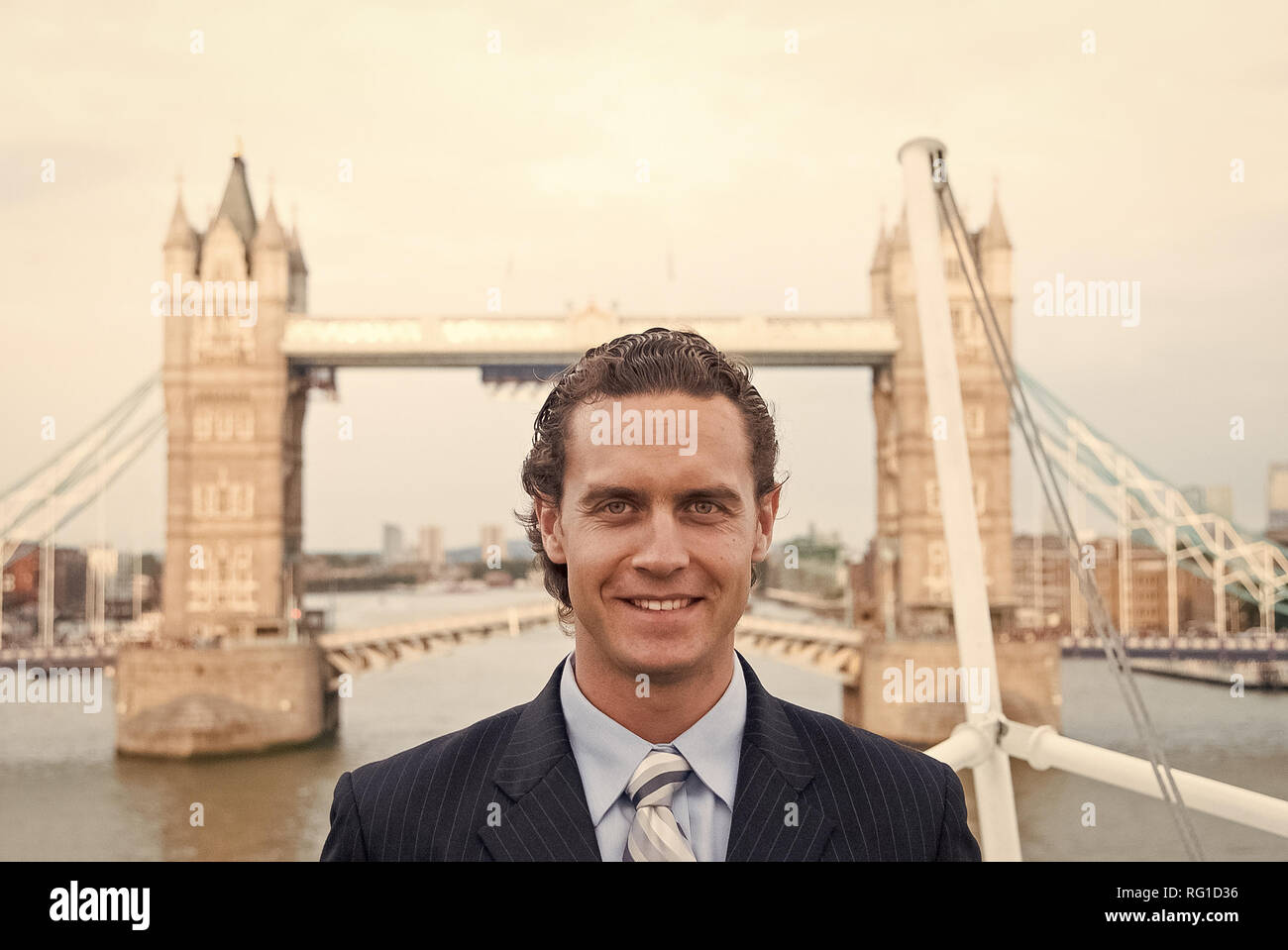 Man smile in London, United Kingdom. Happy businessman at Tower bridge. Tourist enjoy sightseeing in city. Travelling for business and pleasure. Architecture and design concept. - Stock Image