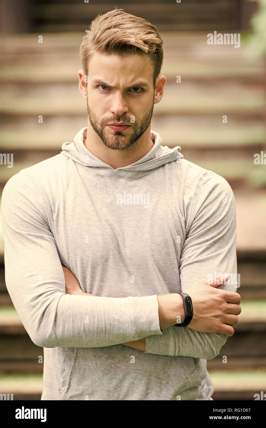 Handsome in style. Man unshaven folded arms looks handsome and cool. Guy bearded attractive cares about appearance. Man bristle serious face, urban background, defocused. Metrosexual concept. - Stock Image
