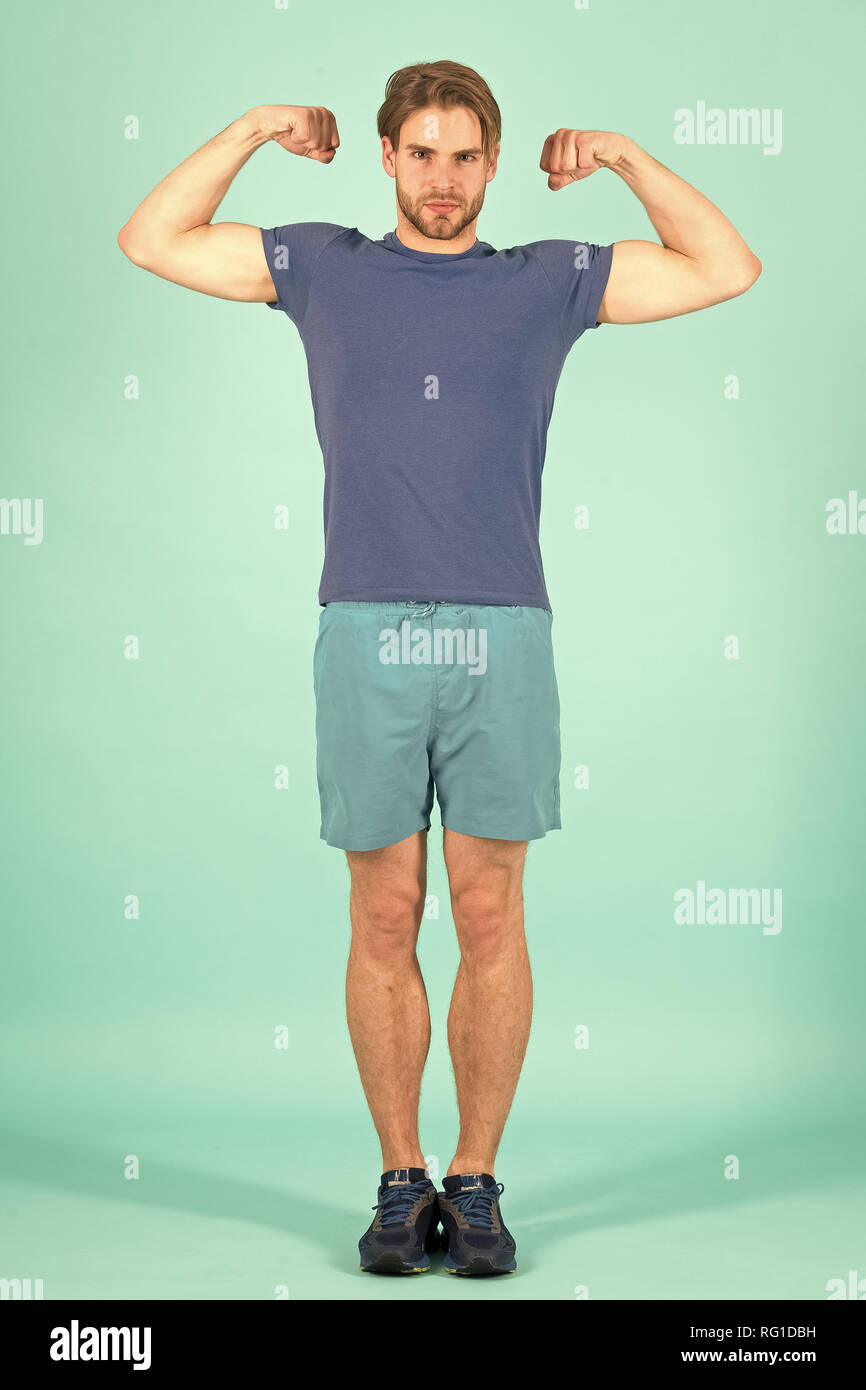 Athlete flex muscles with biceps. Fashion sportsman in blue sport uniform. Bearded man with stylish hair. Power and fitness concept. - Stock Image