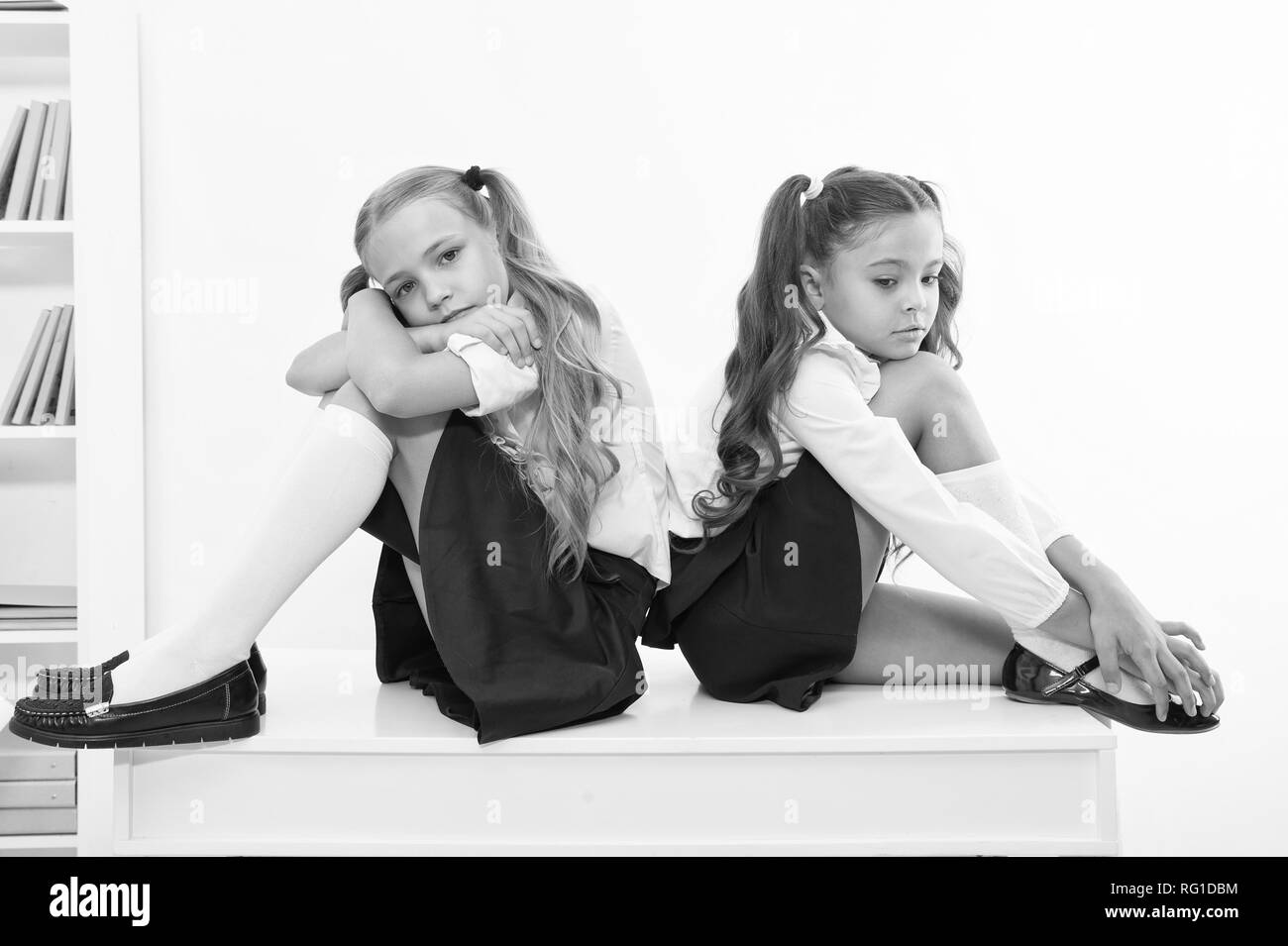 insult. insult of two small girls children or sisters at school. small girls in school uniform - Stock Image