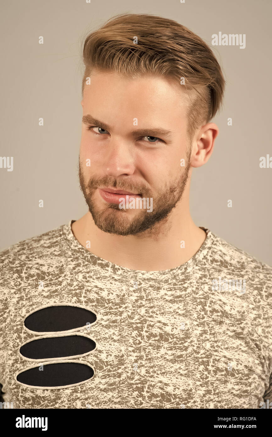 Male beauty concept. Man bearded unshaven guy in stylish shirt with ripped details. Man with bristle cunning face wears fashionable shirt, grey background. Model wears stylish fashionable clothes. - Stock Image