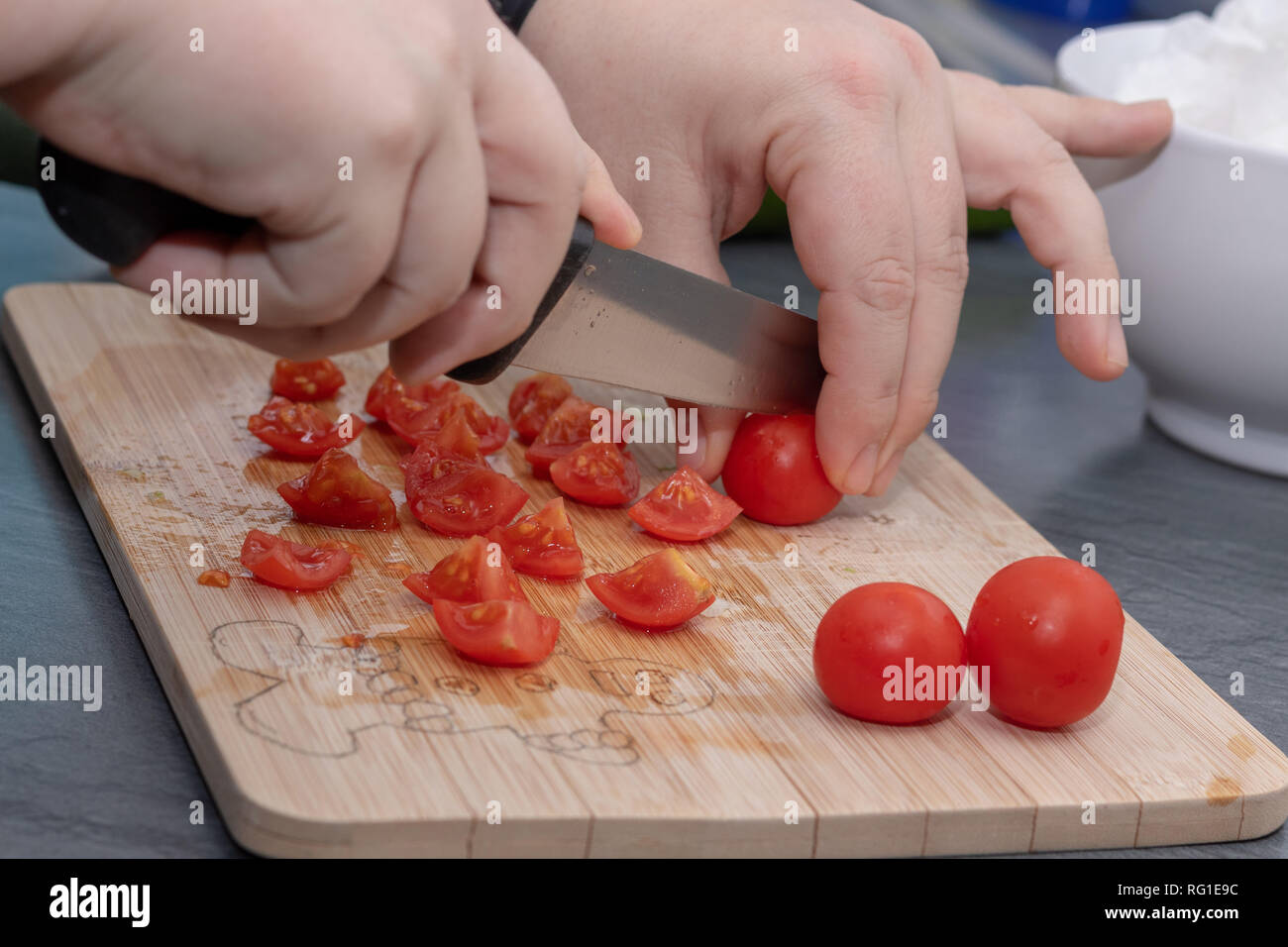 Woman's hands cutting tomato, behind fresh vegetables. - Stock Image