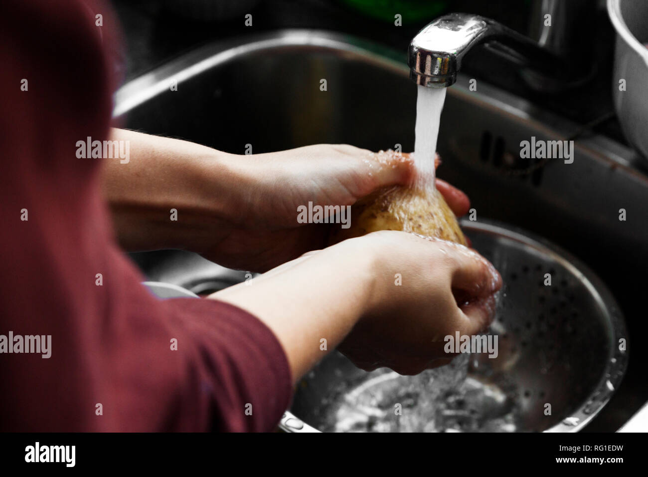 Hand washing potatoes in domestic kitchen sink. - Stock Image