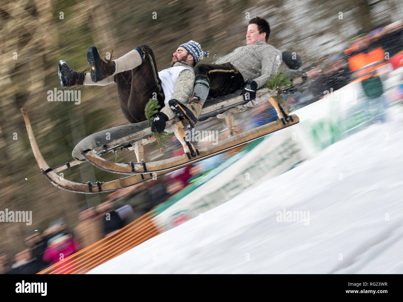 Gaissach, Bavaria, Germany. 27 January 2019, Bavaria, Gaißach: A beak sled with 2 persons as crew jumps past the spectators in the finish area. Based on a bet from 1928, the sledges travel down a 1.5 kilometre stretch. In addition to the driving time, the finish jump on a small natural hill is also evaluated. Mechanical aids such as brakes or controls must not be used. Photo: Peter Kneffel/dpa Credit: dpa picture alliance/Alamy Live News - Stock Image