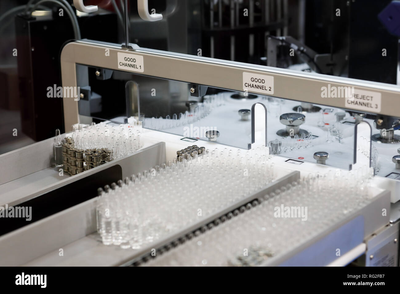 Ampoules quality control at pharmaceutical manufacturing line. Selective focus. - Stock Image