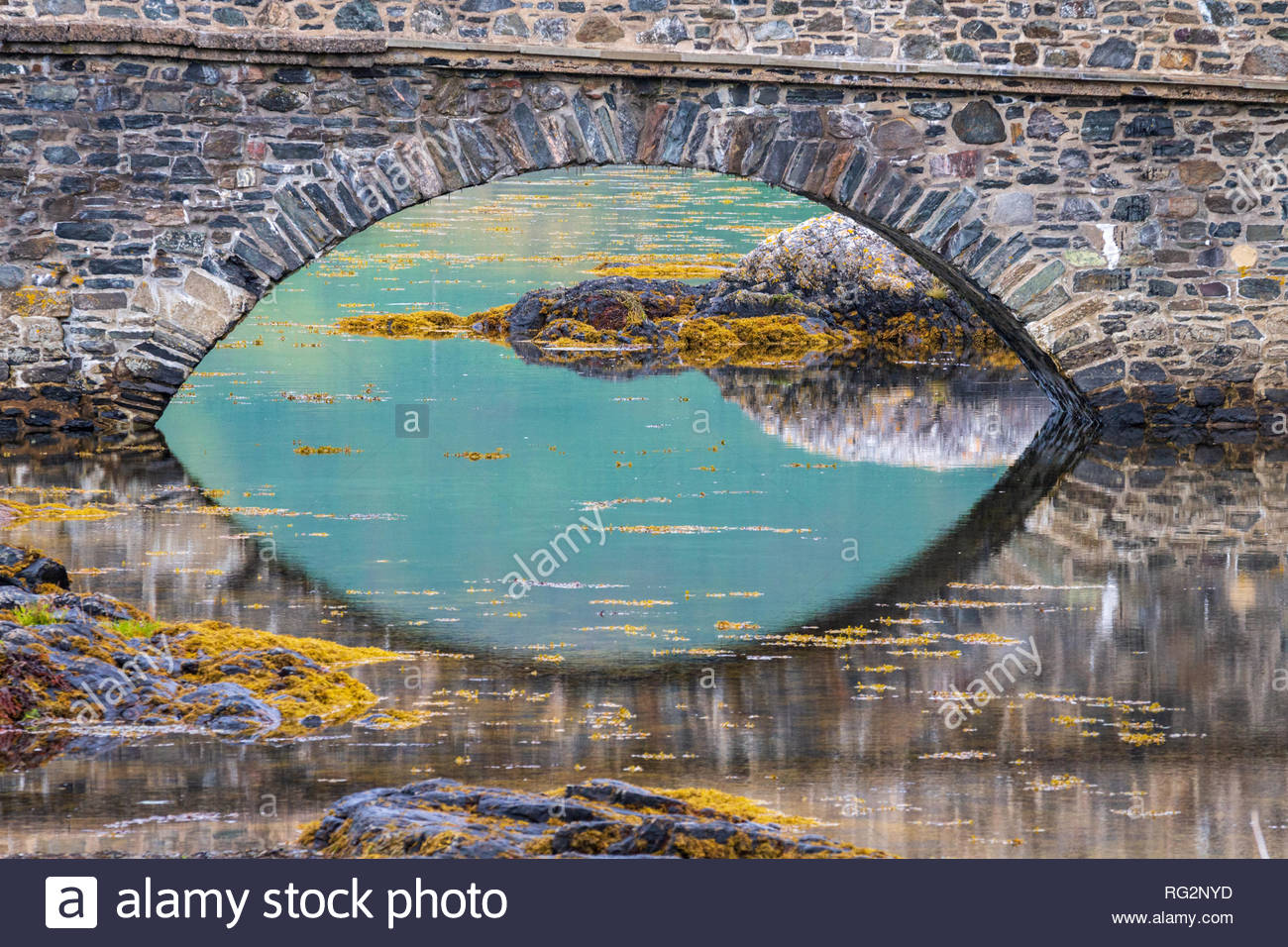 Smooth turquoise water surface beneath Eilean Donan Castle bridge, Scotland. - Stock Image