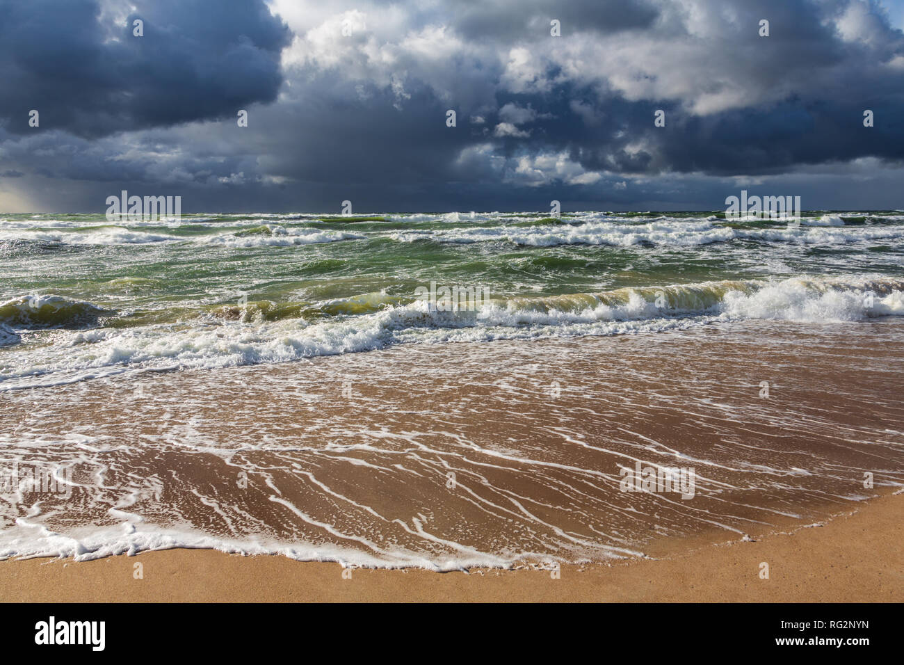 View from the beach to heavy dark rain clouds above the stormy green sea. - Stock Image