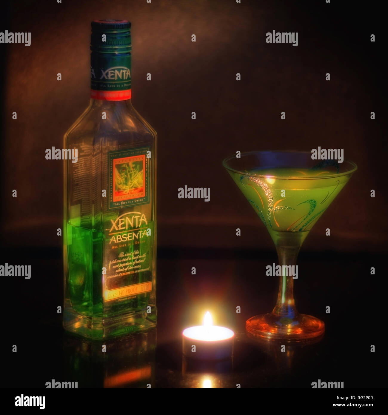 Still-life with a bottle of absinthe, a glass and a candle on the table. Stock Photo