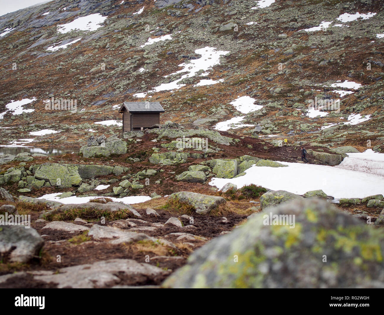 Rescue cabin next to the small pond on the mountain way to the Trolltunga, Norway - Stock Image