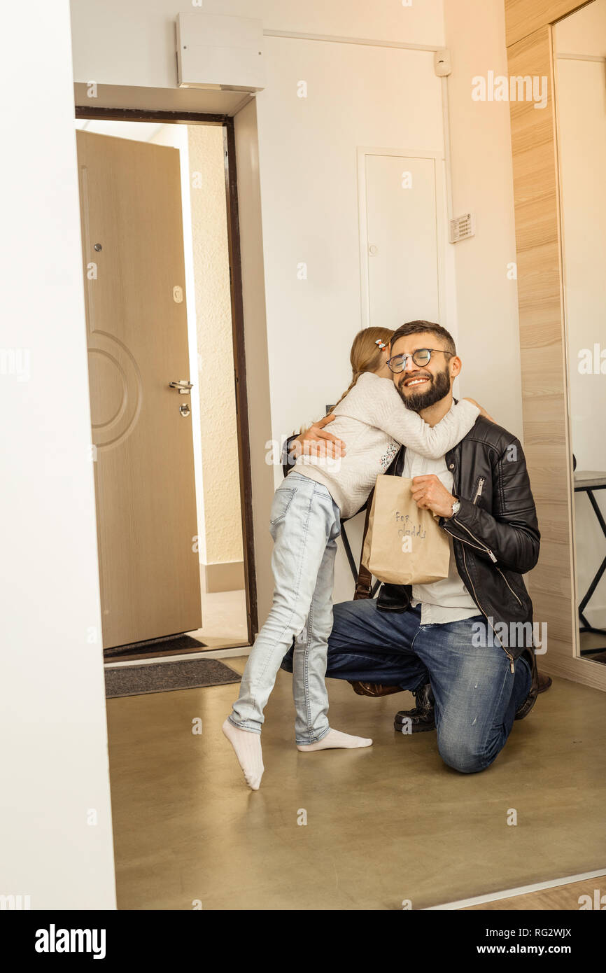 Handsome dark-haired bearded man in eyewear hugging looking happy - Stock Image