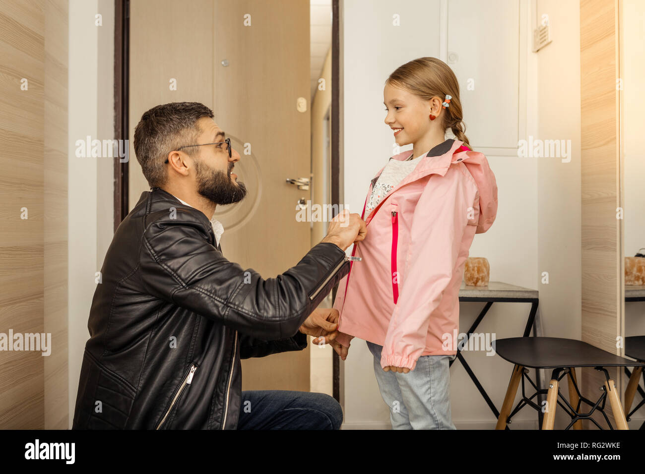 Handsome dark-haired bearded man in eyewear zipping a jacket on his daughter - Stock Image