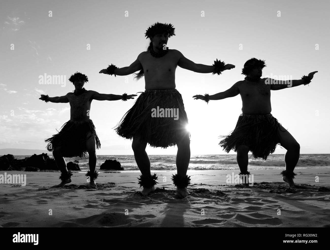 Three male hula dancers on the beach at Chang's Beach, Maui, Hawaii. - Stock Image