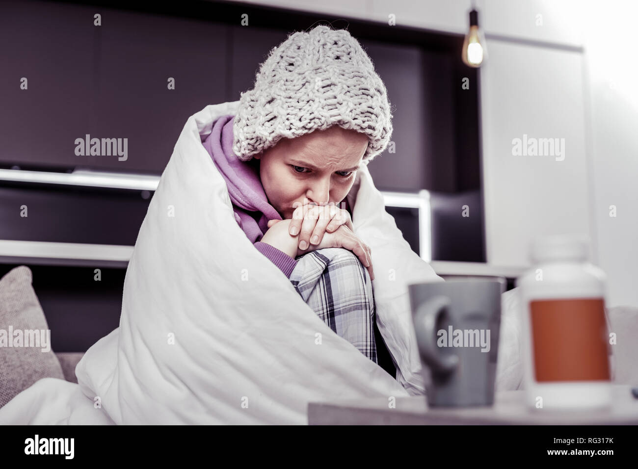 Depressed female person being deep in her thoughts - Stock Image