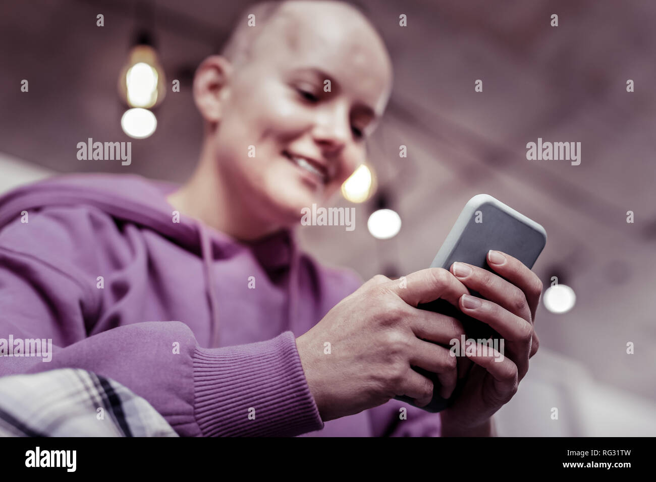 Cheerful bold woman keeping smile on her face - Stock Image