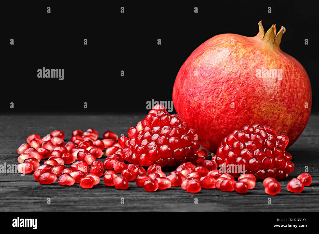 Pomegranate seeds on black wooden table(selective focus). Stock Photo