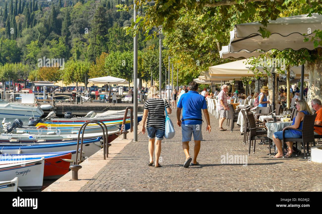 GARDA, ITALY - SEPTEMBER 2018: Two people walking along the promenade in Garda on Lake Garda. Stock Photo
