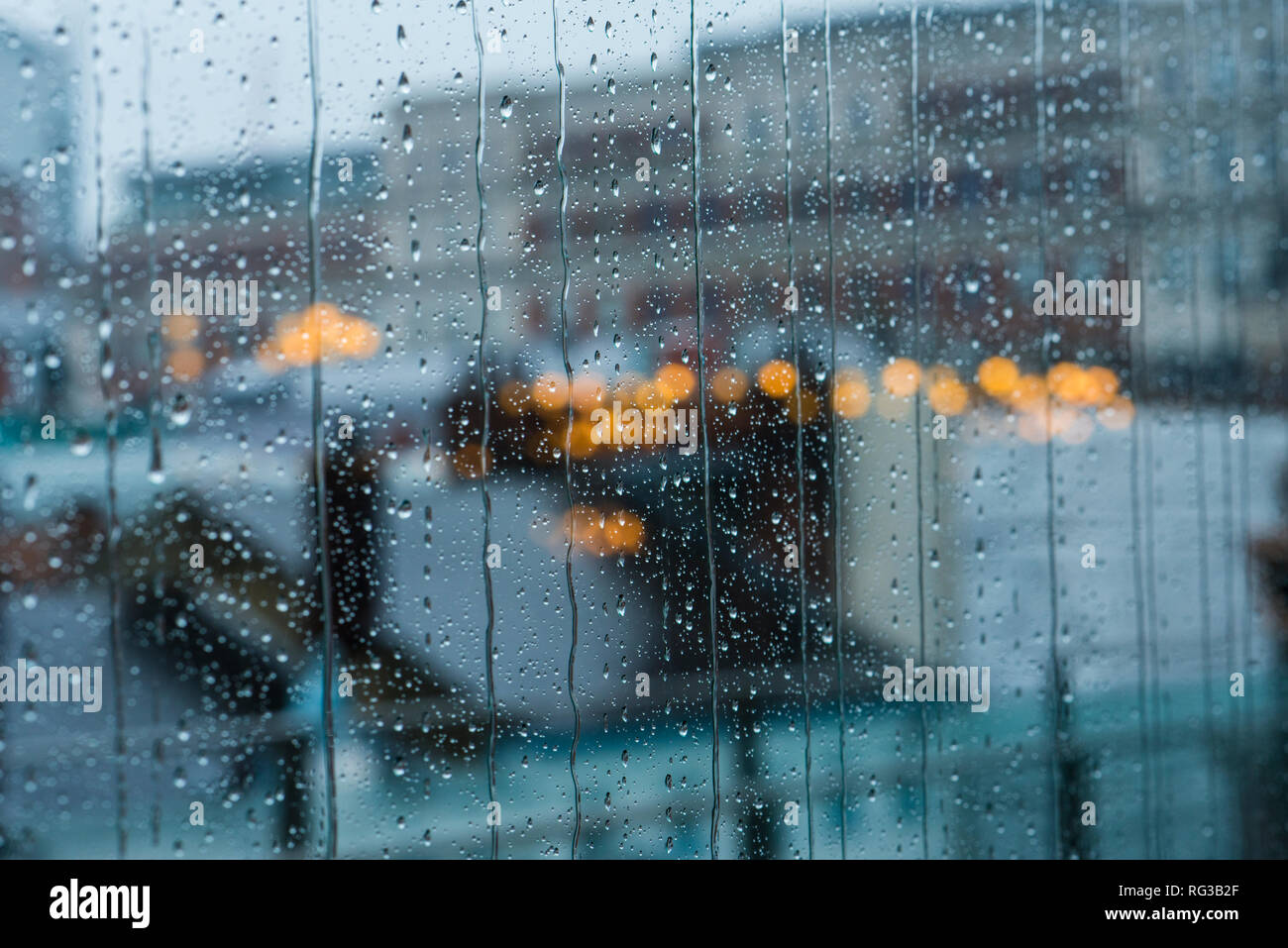 Rain pouring down window pane, defocussed city scene viewed through window, Central Leeds, Yorkshire, England, UK - Stock Image