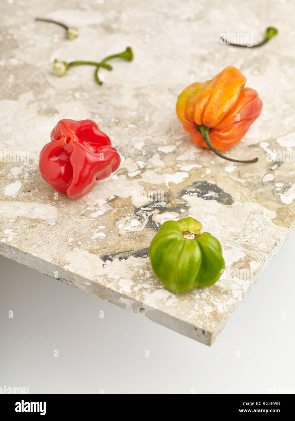 Scotch bonnet pepper and mottled marble surface against light background. Food photograph - Stock Image