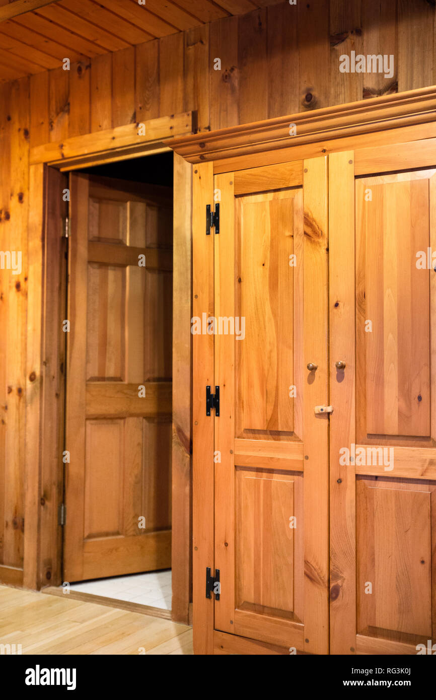 Interior of room with doors and wood paneling inside a beautiful wooden cabin - Stock Image