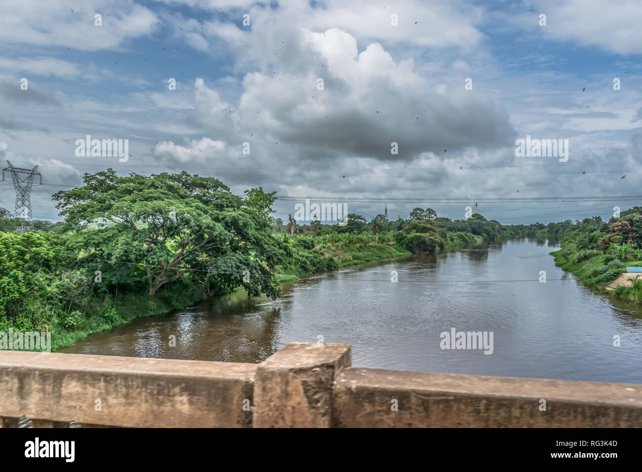 View of the Kwanza (Cuanza) river, tropical vegetation on banks, electric power lines, cloudy sky as background, in Angola - Stock Image
