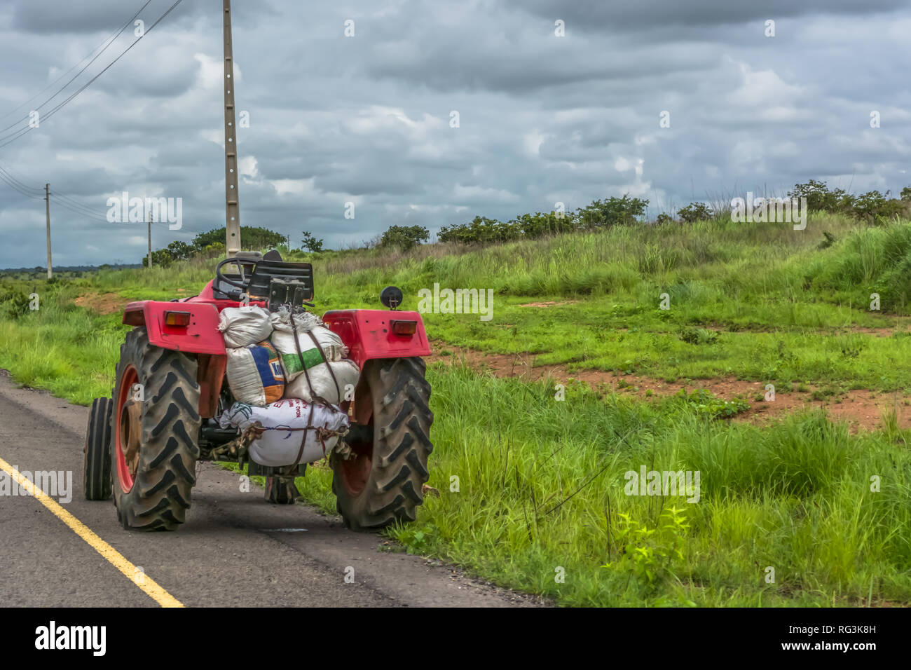 View of a farm tractor on roadside, natural grassland landscape with power lines as background, on Angola - Stock Image