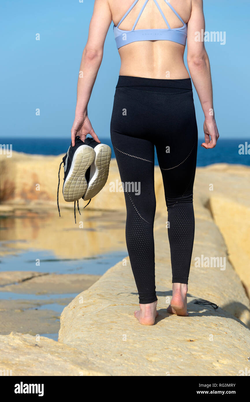 back view of a woman barefoot carrying her trainers walking towards the beach - Stock Image