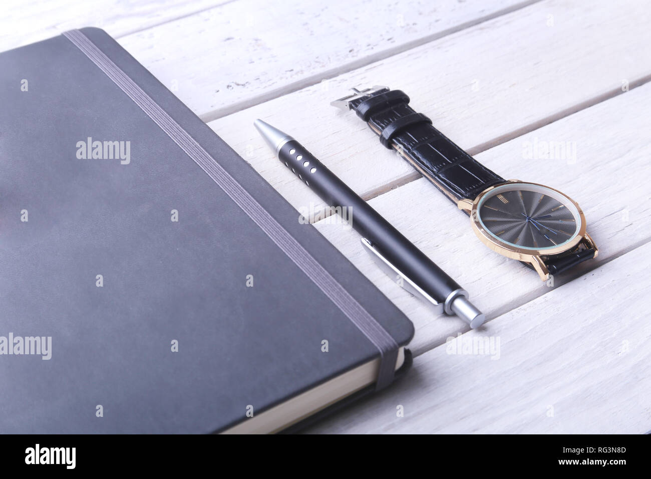 Accessories for business. Watch, notepad and pen on wooden background. Top view composition - Stock Image