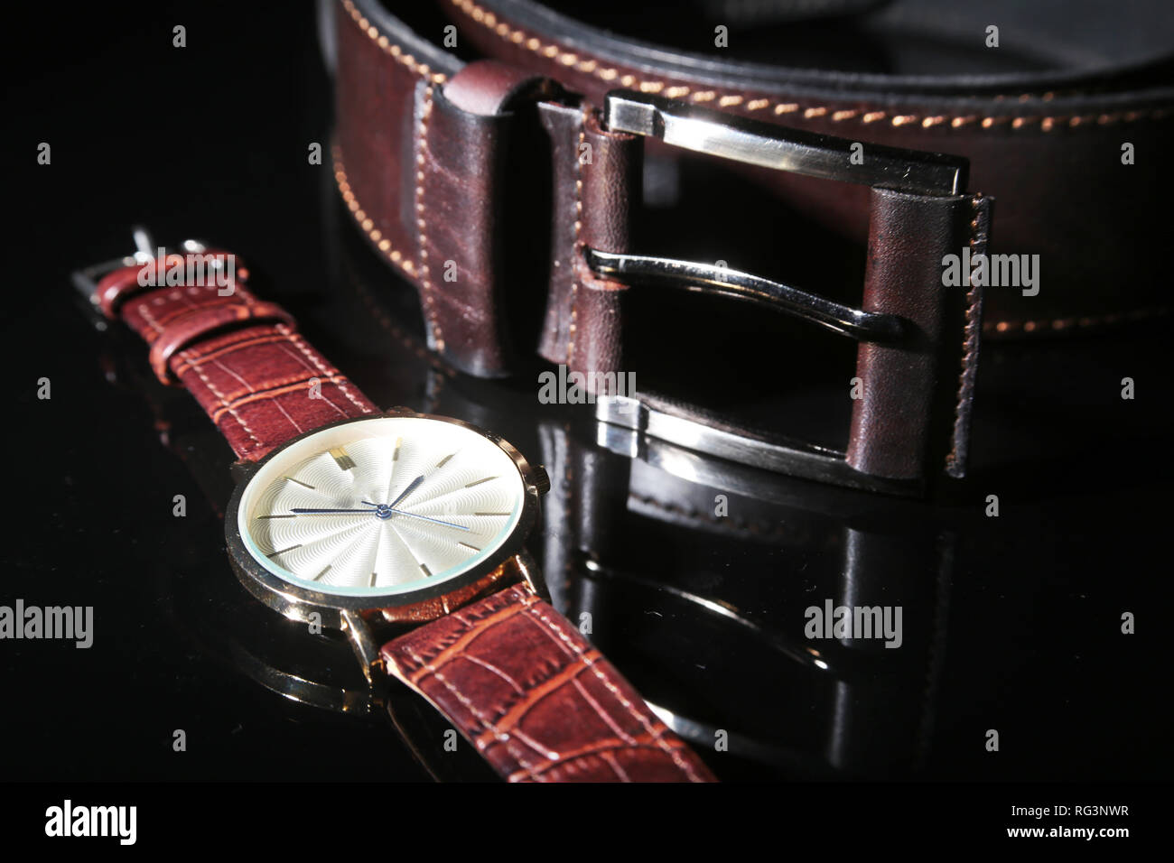 Men's accessories for business and rekreation. Leather belt, Watch, notepad and pen on black mirror background. Top view composition - Stock Image
