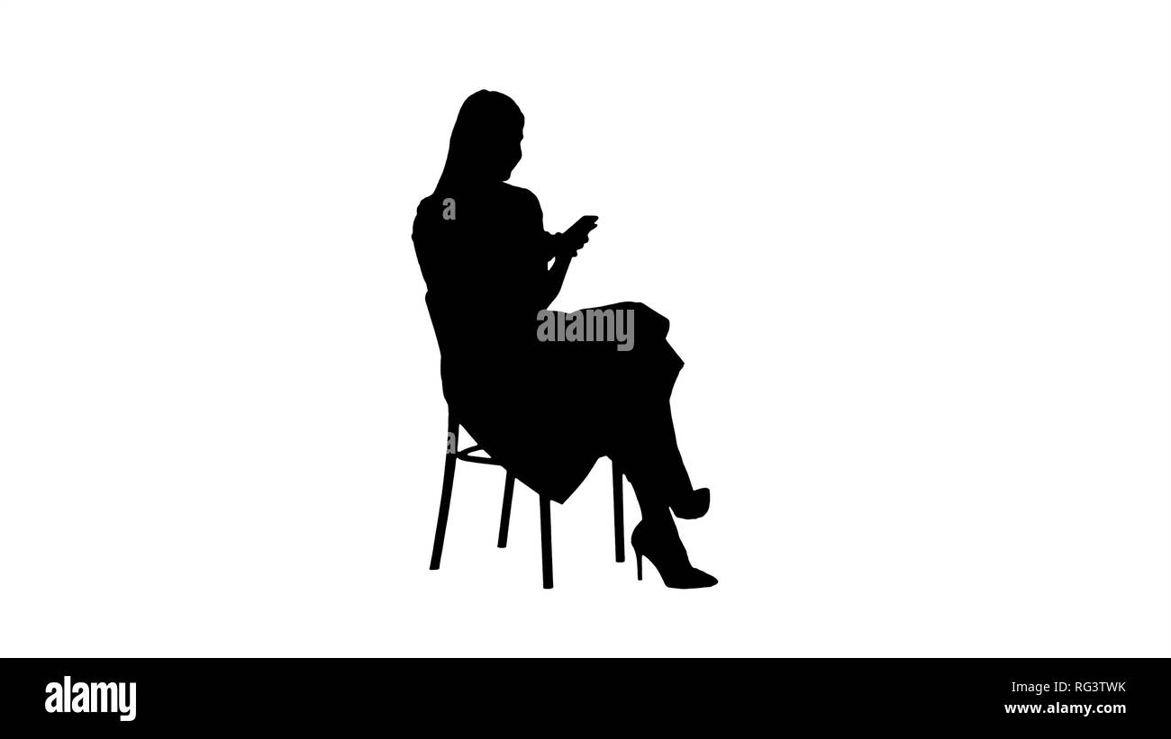 Silhouette Thoughtful woman in pink dress texting on smart phone. Professional shot in 4K resolution. 005. You can use it e.g. in your commercial vide - Stock Image