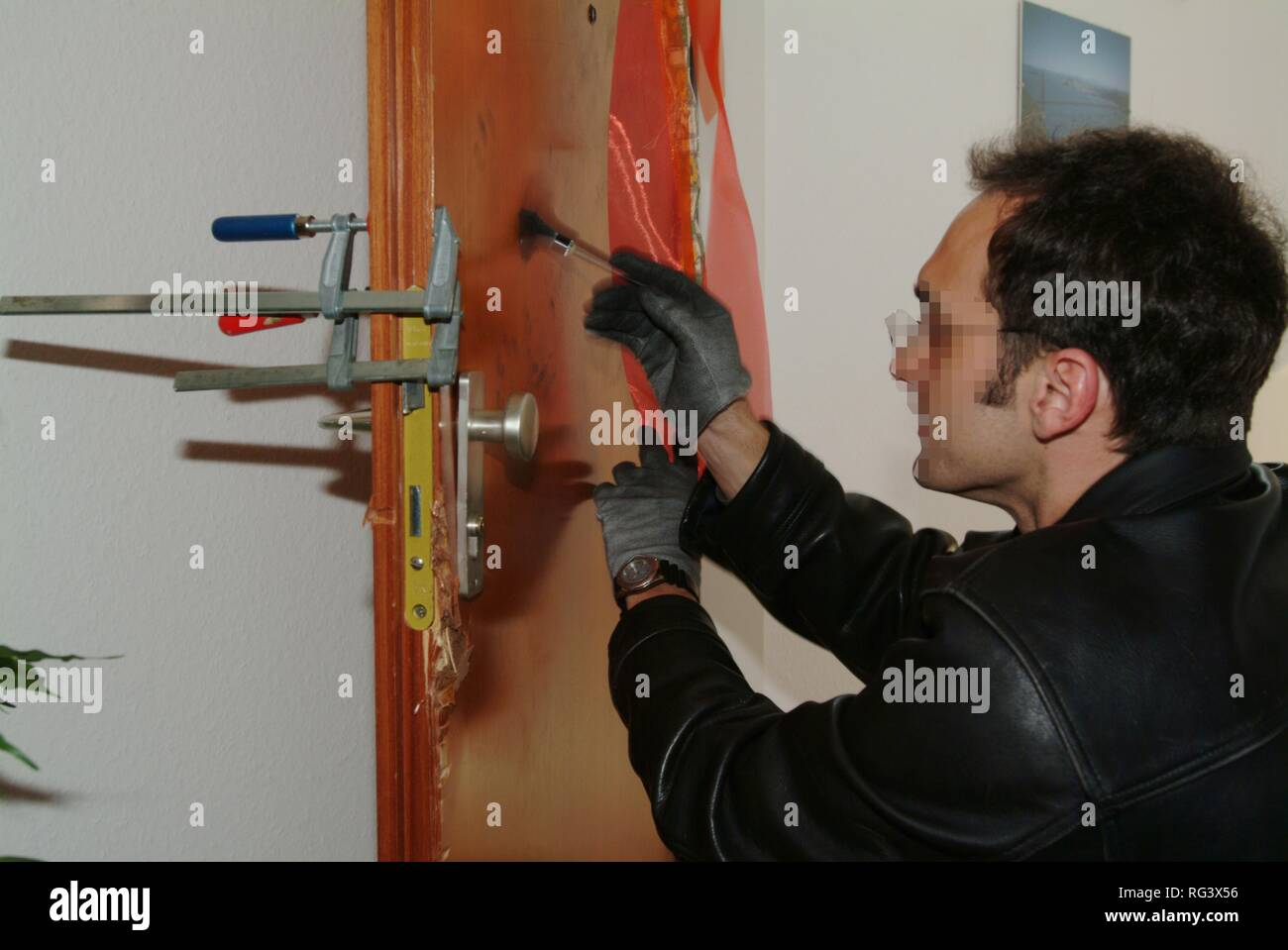 DEU, Germany, NRW: forensic investigator puts coal powder on a broken door, to make fingerprints visible. - Stock Image