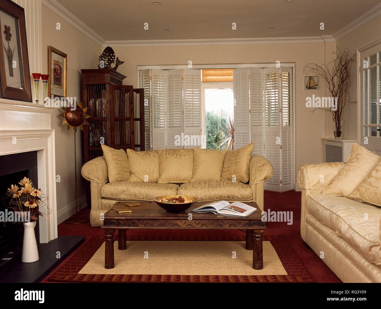 Cream Sofas And Plantation Shutters In Dated Living Room