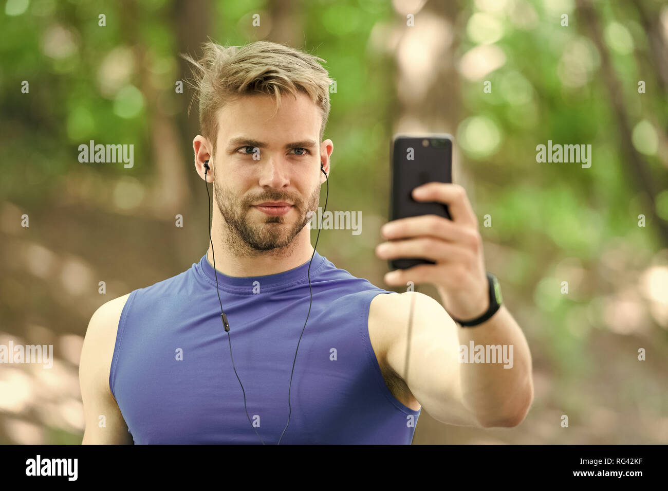 Sport gadget concept. Athlete mobile phone set up playlist before runnig. Man athlete busy face setting up smartphone app, nature background. Sportsman training with pedometer and earphones. - Stock Image